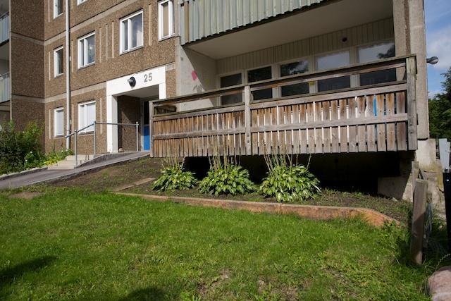 Verandan blev en balkong när marken sjönk undan. Husen står stabilt på pålar men leran runtomkring torkar och marken sjunker.